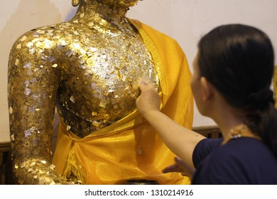 UTTARADIT/THAILAND - FEBRUARY 10, 2019: Hands of women are paste gold leaf sheet on Buddha images. in Wat Phra Than Sila Wat Ard at Uttaradit, Thailand.