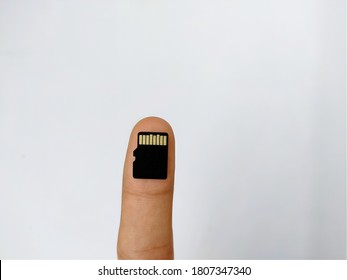 Uttarakhand,India-1June 2020:sd card,black small storage card used in mobile.sd card is kept on a finger tip.sd card with white background.a picture of micro storage device.magic of technology.