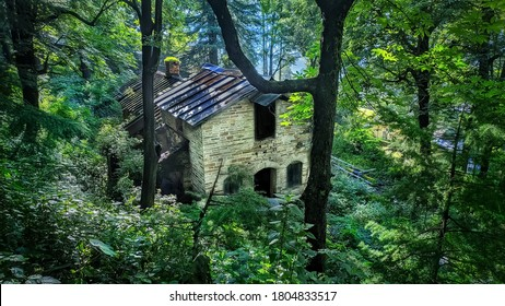 uttarakhand,india:old house in forest.this is a picture of a broken and abandoned house in forest surrounded with trees and greenery.stone house in forest.wallpaper.