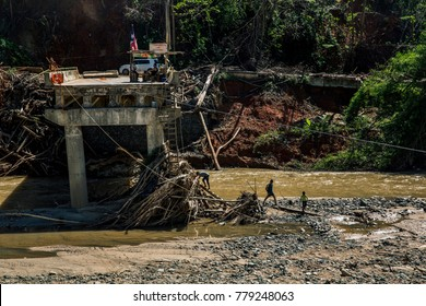 Utuado, Puerto Rico/USA - November 1, 2017:  A family climbs down from a collapsed bridge to get supplies on the other side of the river in the hurricane ravaged rural town of Utuado.