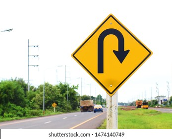 U-turn traffic sign on a pole mounted on the side of the road on the background with a white cloudy sky. With copy space