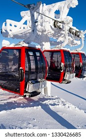 uusamo / Finland - February 2019: Three red gondolas leaving the Saarua Top station in the Ruka ski area on a beautiful and sunny winter day