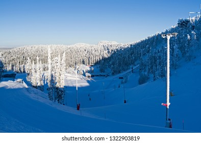 uusamo / Finland - February 2019: View from the upper Talvijarvi slope to the large ski jumping stadium in Ruka on a beautiful and sunny day in February