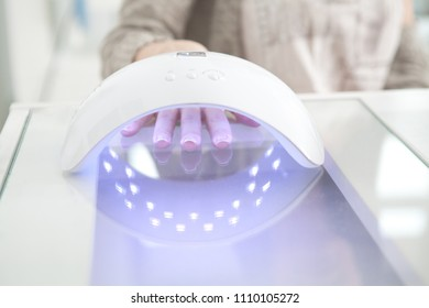 UV lamp gel polish manicure process at nail salon. Close up of woman hand