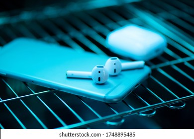UV light sterilization of smartphone and earbuds. COVID-19 prevention concept.