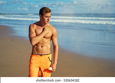 UV protection and suntan. Young handsome man holding bottle with sunscreen lotion on the sea beach.