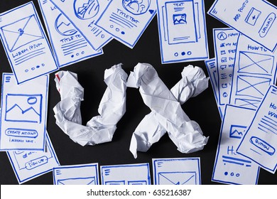 UX letters made of crumpled paper, designer desk with mobile application screen sketches. User experience design creative process