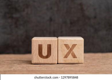 UX User Experience design in product and service concept, cube wooden block building acronym UX on table with blackboard with copy space, user centric method.
