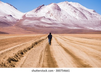 UYUNI, BOLIVIA Circa March 2015: a man running towards the mountaineous landscape