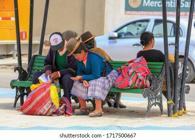 Uyuni, Bolivia - Dec 26, 2018: Indigenous men and women in traditional outfit sitting on a bench in downtown, a small town in southwestern Bolivia and the entry point to the world's largest Salt Flat.