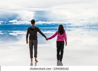 Uyuni, Bolivia- Dec 31, 2018: Man and woman walking away on the lake Salar de Uyuni, Bolivia. America.