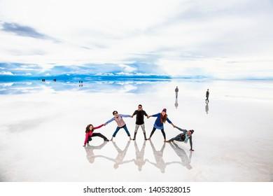 Uyuni, Bolivia- Dec 31, 2018: Group of people make figures with their bodies on the lake Salar de Uyuni, Bolivia. America