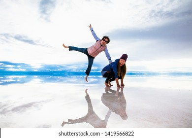 Uyuni, Bolivia- Dec 31, 2018: Mother and daughter make figures with their bodies on the lake Salar de Uyuni, Bolivia. America