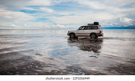 Uyuni, Bolivia, February 2018: offroad car driving through  the water covered Uyuni salt lake during rainy season