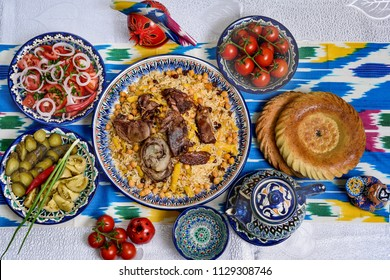 Uzbek cuisine (food) pilaf (plov palov osh) salad achichuk (achuchuk) bread (non lepeshka) tea on uzbek ornament ikat khan-atlas