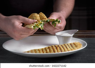 Uzbek East Tatar cuisine, cheburek with suluguni cheese in the hands of a cook on a dark background