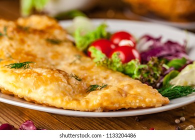 Uzbek eastern Tatar cuisine, cheburek with meat and suluguni cheese in a white plate with vegetables and greens on a wooden table.
