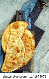 Uzbek eastern Tatar cuisine, cheburek with meat and suluguni cheese and greens on a wooden board. Cheburek - fried pie with meat and onions. Traditional dish of many Turkish and mongolian.  empanada