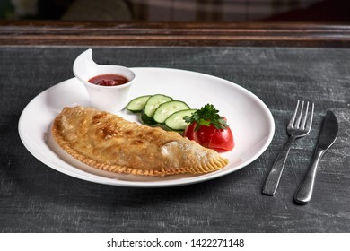 Uzbek eastern Tatar cuisine, cheburek with meat and suluguni cheese in a white plate with vegetables and greens on a dark wooden background.