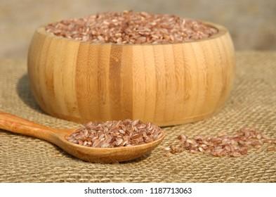 Uzbek rice for pilaf - devzira in a bamboo bowl on burlap closeup