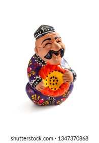Uzbek souvenir - a figure of a mustachioed man in a skullcap with a pumpkin in his hands, in a colored national robe