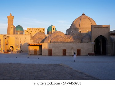 Uzbek woman walking through the streets of ancient Bukhara (Uzbekistan). Early morning. All buildings are illuminated by the rising sun.