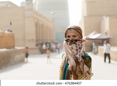 Uzbekistan. Bukhara. Beautiful girl on the street covers her face with a handkerchief