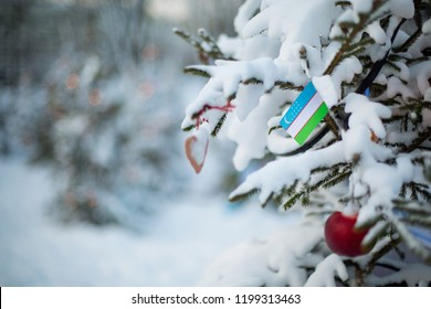 Uzbekistan flag. Christmas background outdoor. Christmas tree covered with snow and decorations and Uzbekistan flag. New Year / Christmas holiday greeting card.
