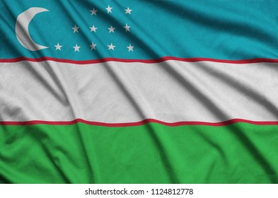 Uzbekistan flag  is depicted on a sports cloth fabric with many folds. Sport team banner