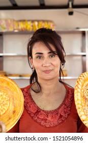 Uzbekistan, Namangan region - May 12,2019 Uzbek beautiful woman sells fresh bread (patir) at the market.