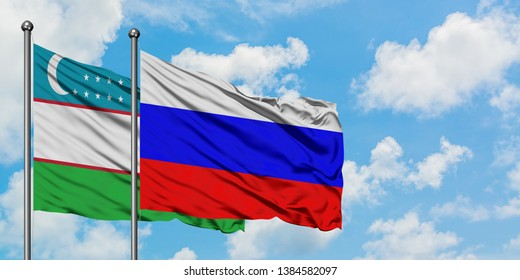 Uzbekistan and Russia flag waving in the wind against white cloudy blue sky together. Diplomacy concept, international relations.