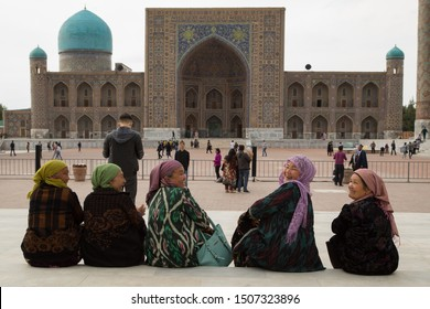 Uzbekistan Samarkand- April 20,2019 Architecture of main square of Samarkand, Uzbekistan. Smiling uzbek women sitting on the Registan Square.