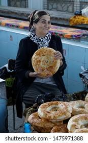 Uzbekistan Samarkand - June 15,2019 Uzbek woman sells fresh bread at the market