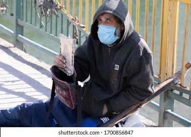 Uzhgorod, Ukraine - Apr. 10, 2020: Beggar cripple in protective medical mask asks for alms holding an icon in his hands