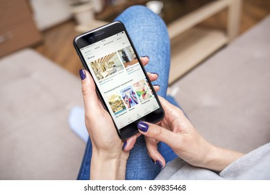 UZHGOROD, UKRAINE - MAY 11, 2017: New black iPhone 7 Plus, with Airbnb, app for booking apartments and hotels in the hands of the woman sitting on the couch, on May 11, 2017 in Uzhgorod, Ukraine.