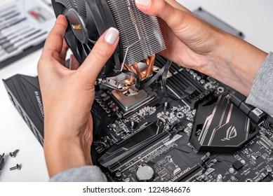 UZHGOROD, UKRAINE - October 25, 2018: Computer installation. The specialist installs a cooler on the new processor Ryzen 7 2700X and computer motherboard Asus rog crosshair vii hero.