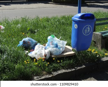 Uzhhorod, Ukraine - April 04 2018: Scattered garbage near a garbage can on a street in Uzhhorod