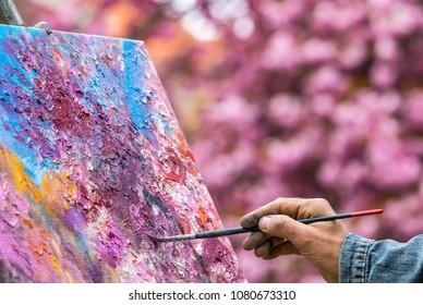 UZHHOROD, UKRAINE - APRIL 14, 2017: Hand of unrecognisable painter artist paints a picture of blooming sakura trees in the center of Uzhhorod city