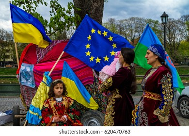 Uzhhorod, Ukraine - April 7, 2017: Participants of the celebration of the International Roma Day in national costumes stand near a cart decorated with the flags of Ukraine and the European Union.