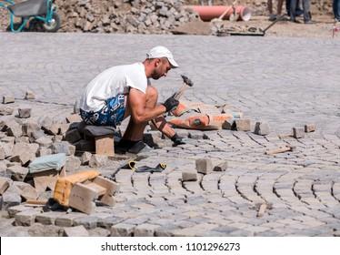 UZHHOROD, UKRAINE - APRIL 8, 2018: Worker making the pavement of stone blocks in the city. Reconstruction of Petefi square in Uzhhorod, Ukraine.