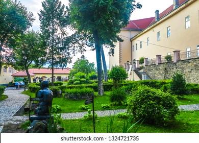 UZHHOROD, UKRAINE  - JULY 2017: Castle Citadel Interior Garden Courtyard Building with Statue of a Man Suffocating a Snake
