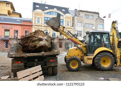 UZHHOROD, UKRAINE - JUNE 27, 2018: Excavator used to dig up tree-stumps and roots in Uzhhorod, Ukraine. Loading of roots on  a dump truck. Reconstruction of Petefi square in the city