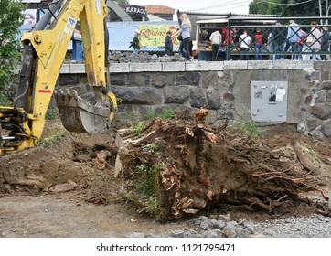 UZHHOROD, UKRAINE - JUNE 27, 2018: Excavator used to dig up tree-stumps and roots in Uzhhorod, Ukraine. Reconstruction of Petefi square in the city