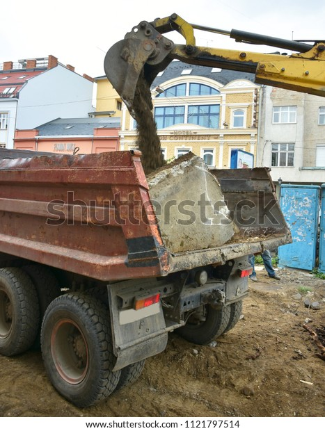 UZHHOROD, UKRAINE - JUNE 27, 2018: Excavator used to dig up tree-stumps and roots in the city. Loading of roots on  a dump truck. Reconstruction of Petefi square in the city