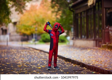 UZHHOROD, UKRAINE - OCTOBER 28, 2017: Young kid in full length deadpool cosplay suit with swords posing on the autumn street