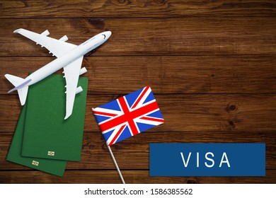 V Britain concept. Text  near passport cover and british flag on wood background top view