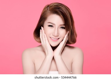 V Shape Face of Asian woman smiling and touching her face. Skincare and Cosmetology concept. pink background.