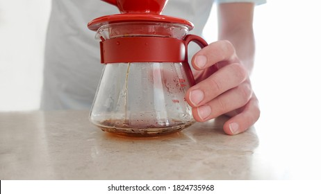 V60, pourover. Homemade coffee. Close-up of dripping coffee into a glass server for making a pourover. Man brews at home V60