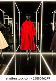 V&A Museum, South Kensington, London - August 30th 2019. (Christian Dior Haute Couture exhibition at the V&A London, 2019). A red coat in a black background with lighting. Exclusive Collection.