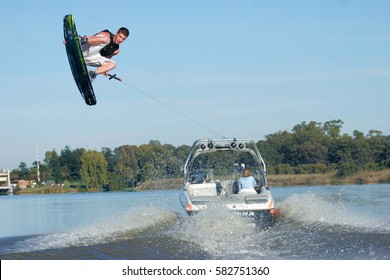 VAAL RIVER, SOUTH AFRICA - 2 MARCH 2012: A male wakeboarder flies across the wake of a boat. Wakeboarding is an extreme sport derived from a combination of waterskiing & surfing. Editorial.